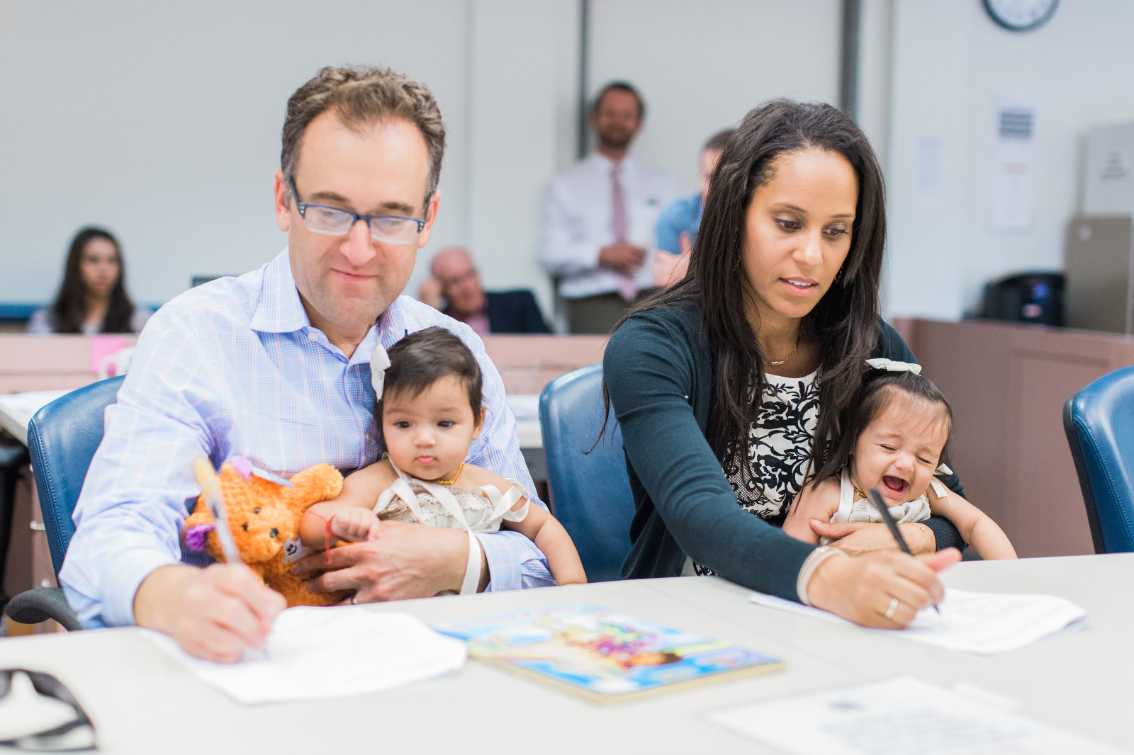 family signs adoption papers while holding babies - charitable adoption photography
